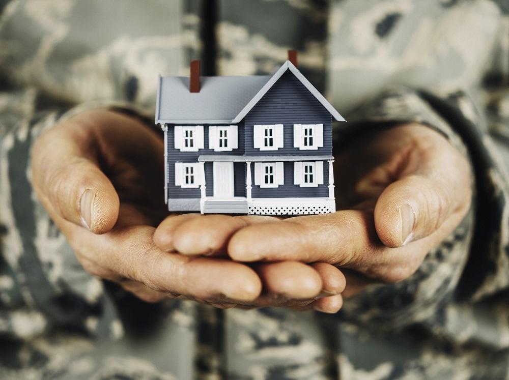 Military service member holding little house.